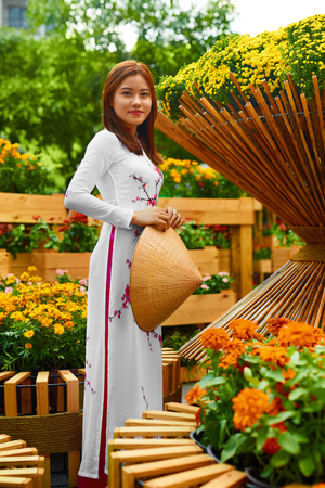 ao: Traditional Clothing Of Vietnam, Asia. Beautiful Happy Asian Girl Dressed In National Traditional Ao Dai Dress ( Costume ), Vietnamese Conical Hat ( Non La, Leaf Hat ) In Flower Garden. Culture.