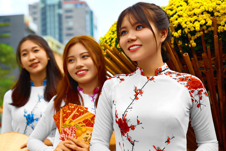 Asian People. Beautiful Happy Smiling Women ( Girls, Friends ) Wearing National Traditional Ao Dai Dresses ( Vietnamese Costume, Clothing ) In Flower Garden, Ho Chi Minh City, Vietnam. Culture Of Asia Stock Photo
