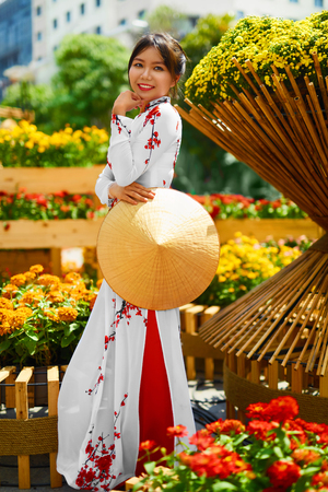 non la: Traditional Clothing Of Vietnam, Asia. Beautiful Happy Asian Girl Dressed In National Traditional Ao Dai Dress ( Costume ), Vietnamese Conical Hat ( Non La, Leaf Hat ) In Flower Garden. Culture.