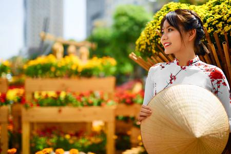 베트남, 아시아의 전통적인 의류. 꽃 정원에서 국립 전통 아오 다이 드레스 (의상), 베트남어 원뿔 모자 (비 라, 잎 모자)을 입고 아름다운 행복 한 아시