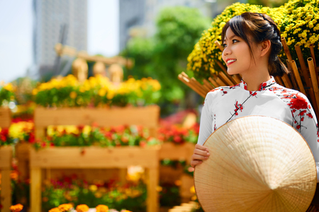 Traditional Clothing Of Vietnam, Asia. Beautiful Happy Asian Girl Dressed In National Traditional Ao Dai Dress ( Costume ), Vietnamese Conical Hat ( Non La, Leaf Hat ) In Flower Garden. Culture.