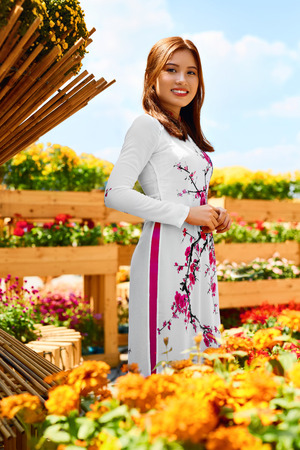 vietnam culture: Asian Beauty Woman. Beautiful Happy Vietnamese Girl Wearing National Traditional White Ao Dai Dress ( Clothing, Costume), Standing In Flower Garden, Ho Chi Minh City, Vietnam. Culture Of Asia
