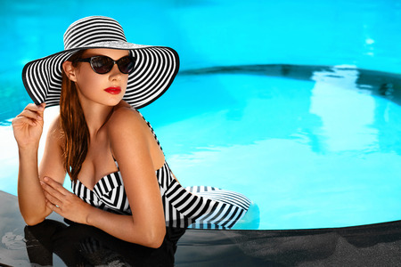 kapelusze: Wakacje. Podróż wakacje w Spa Resort. Piękna Modna Zdrowa młoda kobieta z sexy ciało w bikini, okulary, kapelusz słońce na basen. Zdrowy tryb życia. Uroda, Zdrowie Concept