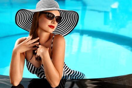 Zomer Vrouw Beauty, Fashion. Mooie gezonde vrouw met sexy lichaam in Elegant Bikini, zonnehoed, zonnebril Ontspannen in Zwembad Op Vakantie Reizen vakantie naar Spa Resort. Summertime Ontspanning Stockfoto