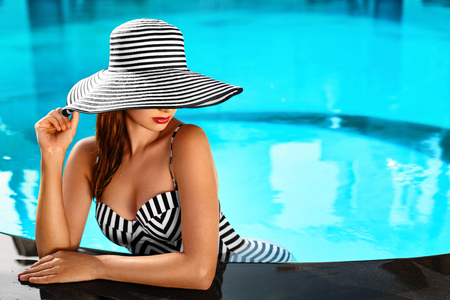 concept hotel: Summer Woman Body Care. Beautiful Sexy Girl With Healthy Skin In Elegant Striped Bikini, Sun Hat Relaxing In Swimming Pool Water In Resort Spa Hotel On Travel Holidays Vacation. Enjoyment. Lifestyle