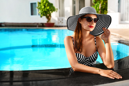 beautiful woman body: Summer Holidays. Travel Vacation To Spa Resort. Beautiful Fashionable Healthy Young Woman With Sexy Body In Bikini, Sunglasses, Sun Hat At Swimming Pool. Healthy Lifestyle. Beauty, Wellness Concept