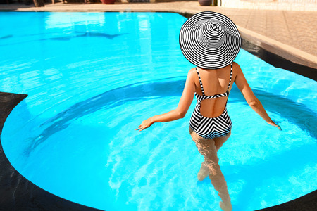 Summer Woman Beauty, Fashion. Beautiful Healthy Woman With Sexy Body In Elegant Bikini, Sun Hat Sunbathing In Luxury Swimming Pool On Holidays Travel Vacation To Spa Resort. Summertime Relaxation