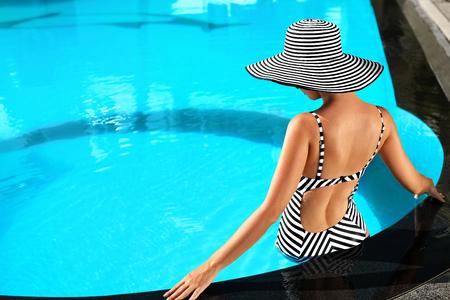 夏の女性の美容、ファッション。スパ リゾートへの休日旅行休暇の豪華なスイミング プールで日光浴太陽帽子エレガントなビキニでセクシーな体と 写真素材