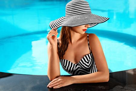 여름 여자 바디 케어. 우아한 스트라이프 비키니에 건강 한 피부와 아름 다운 섹시 소녀, 태양 모자 여행 휴일 휴가에 리조트 스파 호텔에서 수영장 물에서 휴식. 향유. 라이프 스타일 스톡 콘텐츠 - 52696747