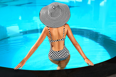 Sommer-Frauen-Körperpflege. Schöne sexy Mädchen mit gesunder Haut in eleganter gestreifter Bikini, Sonnenhut Entspannung im Pool Wasser im Resort Spa Hotel On Travel Urlaub Urlaub. Vergnügen. Lebensstil