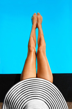 Summer Woman Body Care. Beautiful Sexy Long Fit Female Legs With Healthy Skin In Swimming Pool Water In Resort Spa Hotel On Travel Holidays Vacation. Beauty, Health, Wellness Concept.