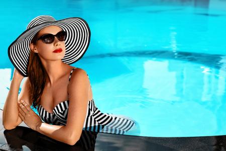 Sommer-Frau Schönheit, Mode. Schöne gesunde Frau mit Sexy Body In eleganter Bikini, Sonnenhut, Sonnenbrille im Swimmingpool sich entspannt auf Urlaub Reisen Urlaub Spa Resort. Sommerzeit Entspannung