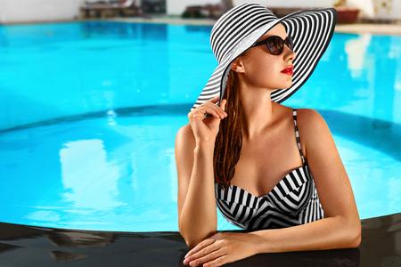 夏の休日。スパ リゾートへの休暇を旅行します。美しいファッショナブルな健康な若い女性のプールでビキニ、サングラス、帽子のセクシーな体。
