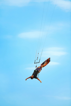 kiteboarding: Extreme Sport. Water Sports. Kiteboarding, Kitesurfing Action. Professional Kiter Makes Difficult Trick In Air. Active Lifestyle. Hobby. Recreational Sporting Activity. Summer Fun, Adventure. Stock Photo