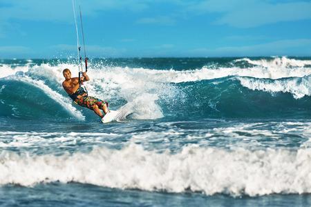 recreational sports: Water Sports. Kiteboarding, Kitesurfing. Surfer Man Surfing On Waves In Ocean, Sea. Extreme Sport Action. Recreational Sporting Activity. Healthy Active Lifestyle. Summer Fun Adventure. Hobby Stock Photo