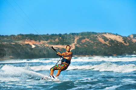 kiteboarding: Water Sports. Kiteboarding, Kitesurfing. Surfer Man Surfing On Waves In Ocean, Sea. Extreme Sport Action. Recreational Sporting Activity. Healthy Active Lifestyle. Summer Fun Adventure. Hobby Stock Photo