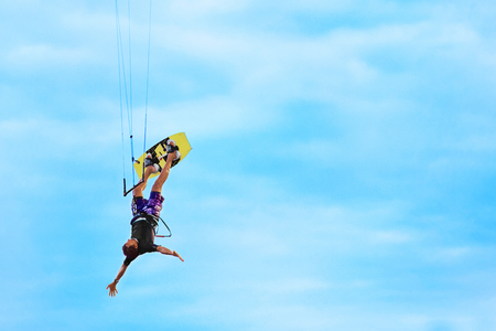 kiter: Extreme Sport. Water Sports. Kiteboarding, Kitesurfing Action. Professional Kiter Makes Difficult Trick In Air. Active Lifestyle. Hobby. Recreational Sporting Activity. Summer Fun, Adventure. Stock Photo