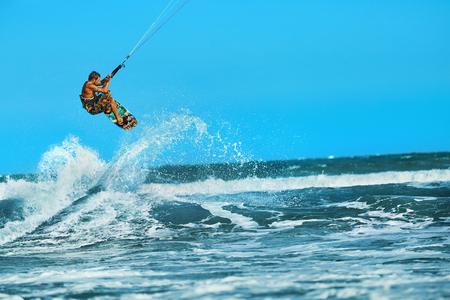 Acción de recreo Deportes acuáticos. El hombre sano (Surfer) Kiteboarding (Kitesurfing) En Olas en el mar, el océano. Deporte extremo. Diversión del verano, de vacaciones. Estilo de vida activo. Ocio Actividad Deportiva. Hobby Foto de archivo