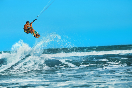 Recreational Water Sports Action. Healthy Man ( Surfer ) Kiteboarding ( Kite Surfing ) On Waves In Sea, Ocean. Extreme Sport. Summer Fun, Vacation. Active Lifestyle. Leisure Sporting Activity. Hobby Stock Photo - 53264724