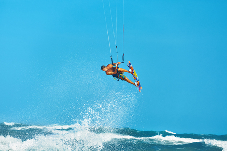 kiteboarding: Recreational Water Sports Action. Healthy Man ( Surfer ) Kiteboarding ( Kite Surfing ) On Waves In Sea, Ocean. Extreme Sport. Summer Fun, Vacation. Active Lifestyle. Leisure Sporting Activity. Hobby