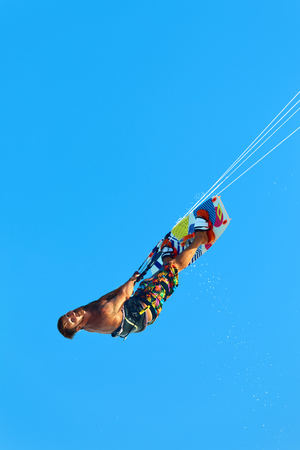 sporting activity: Extreme Water Sport. Kiteboarding, Kitesurfing Action. Professional Kiter Makes Difficult Trick In Air. Active Lifestyle. Hobby. Recreational Sporting Activity. Sports. Summer Fun, Adventure.