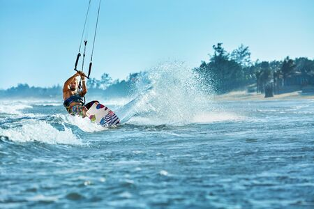 sporting activity: Water Sports. Kiteboarding, Kitesurfing. Surfer Man Surfing On Waves In Ocean, Sea. Extreme Sport Action. Recreational Sporting Activity. Healthy Active Lifestyle. Summer Fun Adventure. Hobby Stock Photo