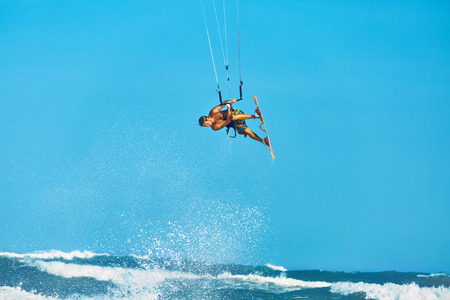 sporting activity: Recreational Water Sports Action. Healthy Man ( Surfer ) Kiteboarding ( Kite Surfing ) On Waves In Sea, Ocean. Extreme Sport. Summer Fun, Vacation. Active Lifestyle. Leisure Sporting Activity. Hobby
