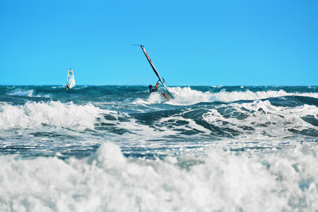 sporting activity: Recreational Water Sports. Windsurfing. Windsurfer Surfing The Wind On Waves In Ocean, Sea. Extreme Sport Action. Recreational Sporting Activity. Healthy Active Lifestyle. Summer Fun Adventure. Hobby