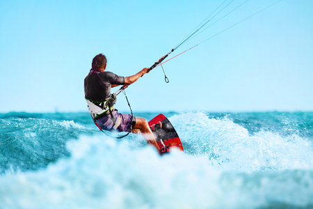 kiter: Kiteboarding, Kitesurfing. Water Sports. Professional Kite Surfer In Action On Waves In Ocean. Extreme Sport. Healthy Active Lifestyle. Hobby. Recreational Sporting Activity. Summer Fun, Adventure Stock Photo
