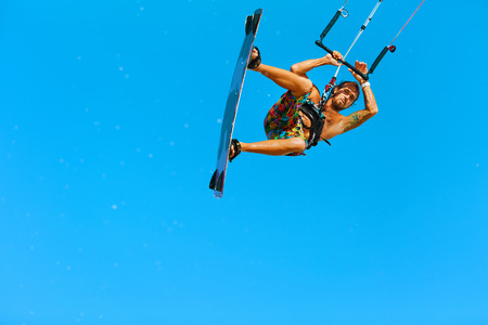 sporting activity: Kiteboarding, Kitesurfing. Water Sports. Professional Kite Surfer In Action In Air. Extreme Sport In Ocean. Healthy Active Lifestyle. Recreational Sporting Activity. Summer Fun, Hobby. Adrenaline.