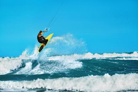 papalote: Acción de recreo Deportes acuáticos. El hombre sano (Surfer) Kiteboarding (Kitesurfing) En Olas en el mar, el océano. Deporte extremo. Diversión del verano, de vacaciones. Estilo de vida activo. Ocio Actividad Deportiva. Hobby Foto de archivo
