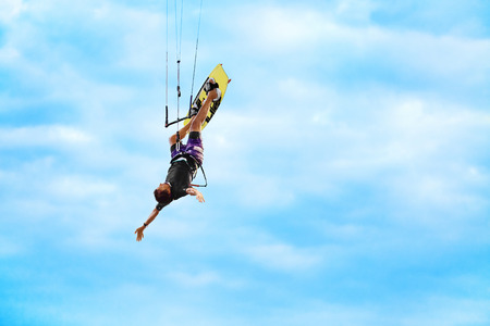 jumps: Extreme Sport. Water Sports. Kiteboarding, Kitesurfing Action. Professional Kiter Makes Difficult Trick In Air. Active Lifestyle. Hobby. Recreational Sporting Activity. Summer Fun, Adventure. Stock Photo