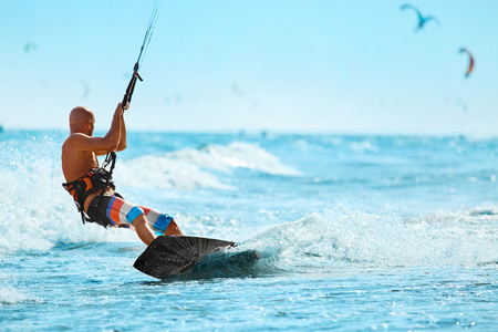 kiter: Recreational Sports. Healthy Man Kiteboarding ( Kite Surfing ) On Waves In Sea Water. Extreme Sport Action. Summer Fun, Adventure, Holidays Travel Vacation. Active Lifestyle. Leisure Sporting Activity