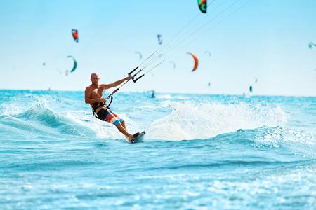 Recreatieve Sporten. Gezonde Mens Kiteboarding (Kitesurfen) op de golven in het zeewater. Extreme Sport Actie. Summer Fun, Avontuur, Vakantie Reizen Vakantie. Actieve levensstijl. Leisure Sporting Activity Stockfoto