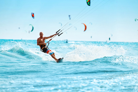 Recreational Sports. Healthy Man Kiteboarding ( Kite Surfing ) On Waves In Sea Water. Extreme Sport Action. Summer Fun, Adventure, Holidays Travel Vacation. Active Lifestyle. Leisure Sporting Activity