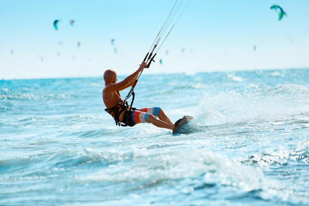 sporting activity: Kiteboarding, Kitesurfing. Water Sports. Professional Kite Surfer In Action On Waves In Ocean. Extreme Sport. Healthy Active Lifestyle. Hobby. Recreational Sporting Activity. Summer Fun, Adventure Stock Photo