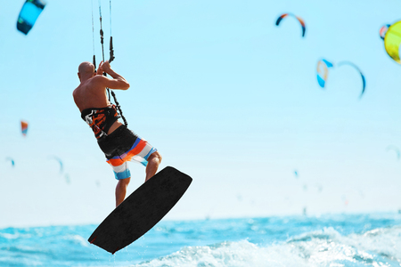 kiter: Water Sports. Kiteboarding, Kitesurfing. Kiter Jumping On Waves In Ocean. Extreme Sport Action. Recreational Sporting Activity. Healthy Active Lifestyle. Summer Fun, Adventure, Travel Vacation. Hobby