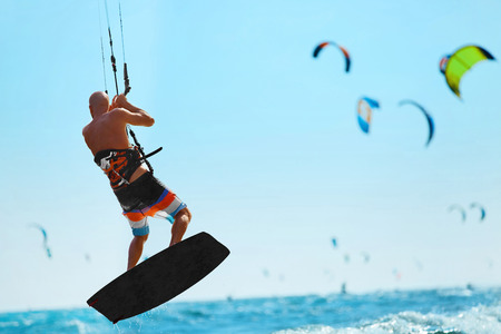 kiteboarding: Water Sports. Kiteboarding, Kitesurfing. Kiter Jumping On Waves In Ocean. Extreme Sport Action. Recreational Sporting Activity. Healthy Active Lifestyle. Summer Fun, Adventure, Travel Vacation. Hobby