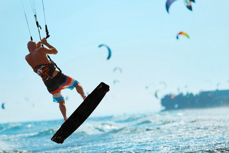 sporting activity: Water Sports. Kiteboarding, Kitesurfing. Kiter Jumping On Waves In Ocean. Extreme Sport Action. Recreational Sporting Activity. Healthy Active Lifestyle. Summer Fun, Adventure, Travel Vacation. Hobby