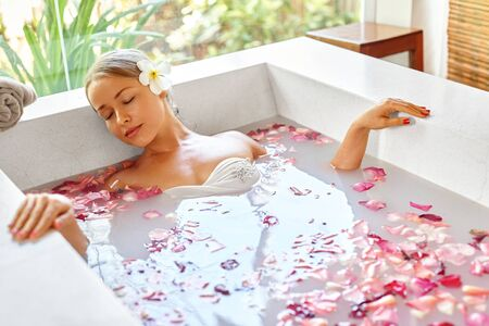 woman in bath: Wellness. Skin, Body Care Spa Therapy. Closeup Beautiful Blonde Young Woman In Bikini Relaxing In Flower Rose Bath Tub In Renew Day Spa Salon. Beauty Treatment. Aromatherapy, Healthy Lifestyle Concept