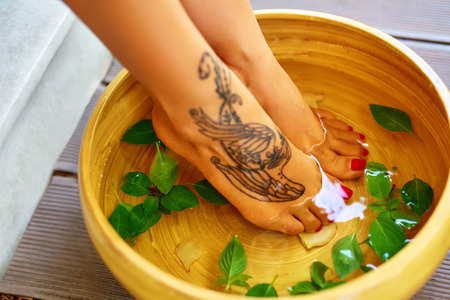 Body Care. Female Feet In Basin, Bowl Bath With Water, Peppermint, Ginger, Essential Oil. Spa Pedicure Procedure. Relaxing Detox Foot Aromatherapy Treatment In Beauty Salon. Healthy Skin Therapy