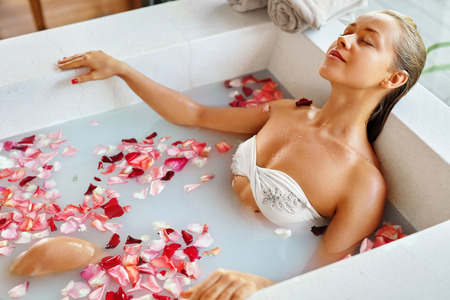 woman bath: Spa Relaxation. Woman Body Care. Beautiful Sexy Caucasian Blonde Girl In Bikini Lying In Flower Bath In Resort Day Spa Salon. Beauty Treatment, Skin Care Therapy. Wellness. Healthy Lifestyle Concept
