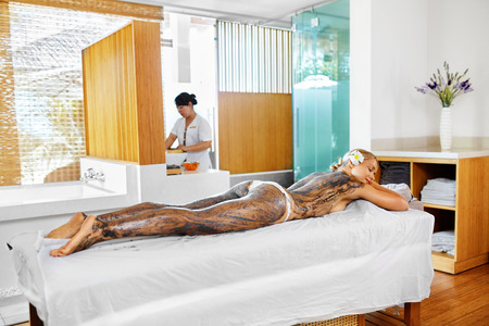 Body Care. Spa Treatment. Beautiful Sexy Young Woman Receiving Cosmetic Clay, Marine Algae Body Mask Lying On Massage Table At Beauty Salon. Skin Care Wrap Therapy. Healthy Lifestyle, Wellness Concept