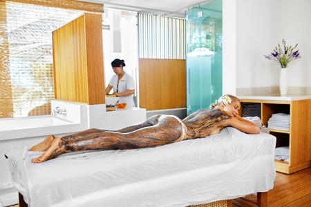 wraps: Cuidado del cuerpo. Tratamiento de spa. Hermosa atractiva mujer joven que recibe el cosmética de la arcilla, algas marinas cuerpo de la máscara que yace en mesa de masaje en el salón de belleza. Cuidado de la piel del abrigo de la terapia. Estilo de vida saludable, el concepto de bienestar Foto de archivo
