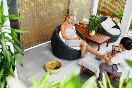 Spa Foot Massage. Body, Skin Care Treatment. Beautiful Woman Getting Relaxing Aromatherapy Oil Feet Massage Outside In Spa Salon Garden. Beauty Therapy, Procedure Concept. Wellness, Healthy Lifestyle Archivio Fotografico