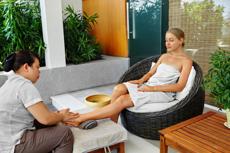 woman foot: Spa Foot Massage. Body, Skin Care Treatment. Beautiful Woman Getting Relaxing Aromatherapy Oil Feet Massage Outside In Spa Salon Garden. Beauty Therapy, Procedure Concept. Wellness, Healthy Lifestyle Stock Photo