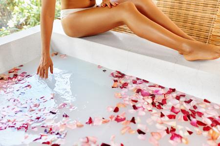 mujer con rosas: Piernas de la mujer. Cuidado del cuerpo. Primer plano de mujeres hermosas piernas Cerca bañera llena de pétalos de rosa, tratamiento Cuidado de la piel de la flor en salón del balneario. Bienestar, estilo de vida saludable, procedimiento de relajación. Foto de archivo