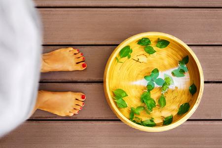 pies: Cuidado del cuerpo. Pies femeninos en Spa Procedimiento pedicura. Pie de la Cuenca del baño, recipiente con agua, menta, jengibre, aceites esenciales para aromaterapia tratamiento relajante en el salón. Terapia de la piel, estilo de vida saludable