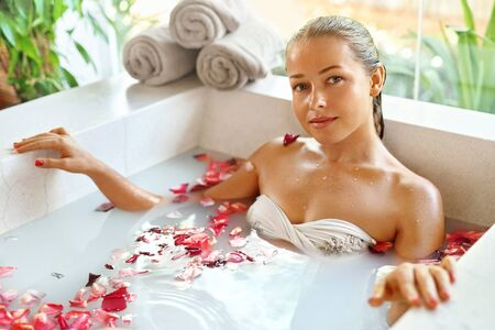 woman in bath: Beauty Woman Spa Body Care Treatment. Closeup Portrait Of Beautiful Smiling Model Girl Relaxing In Flower Bath Tub In Salon. Skin Care, Cleansing Procedure Concept. Healthy Lifestyle, Wellness