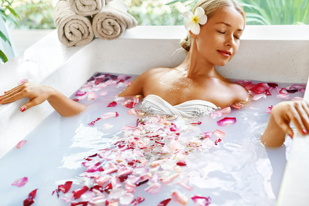 bath: Health And Beauty. Woman Spa Body Care Procedure. Closeup Attractive Sexy Blonde Female In Bikini Relaxing In Flower Rose Bath In Day Spa Centre. Beauty Treatment, Skincare Therapy Concept. Wellness